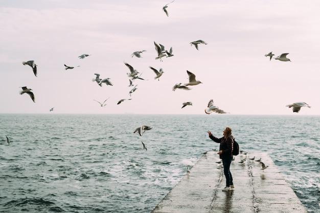 Девушка стоит возле моря на пирсе с рюкзаком и кормит чаек.