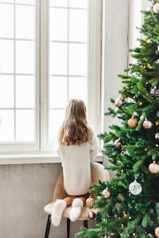 女の子は窓の近くに立って、通りを見て、インテリアはクリスマスに装飾されています