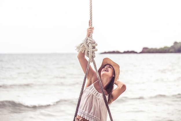 タイのビーチのブランコに立っている女の子