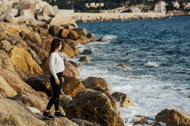 Девушка стоит на камнях у побережья лазурного берега в ницце, франция