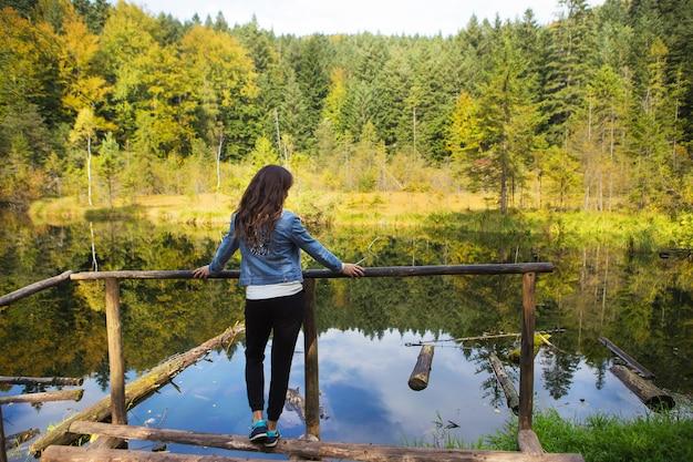 女の子は橋の上に立って湖を見ます-カルパティア山脈、ウクライナ。