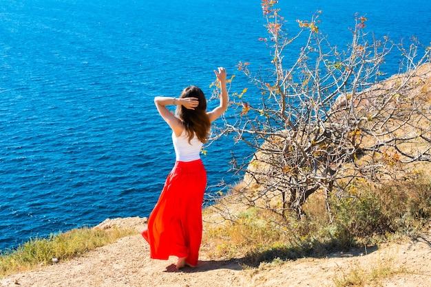 소녀는 절벽의 가장자리에 선다. 화창한 날씨에 여름에 케이프 fiolent. 크리미아, 러시아. 많은 배와 배. 산, 바다. 청록색 수채화.