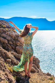 Девушка стоит на краю обрыва. мыс фиолент летом в солнечную погоду. крым, россия.