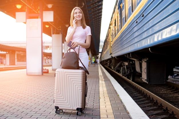 Девушка стоит на перроне вокзала с чемоданом и ждет поезд, студент едет, уезжает на летние каникулы, копирует пространство