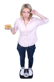 The girl stands on the scales and eat fast food.