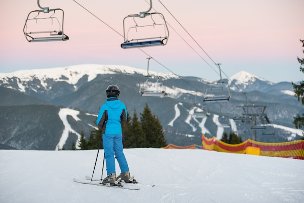 Girl stands on skis under the ski-lift with her back