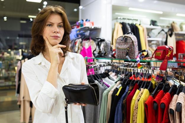 여자는 부티크의 한가운데에 그녀의 손에 지갑으로 신중하게 서 있습니다.
