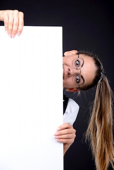 The girl stands behind a white sheet and smiles.