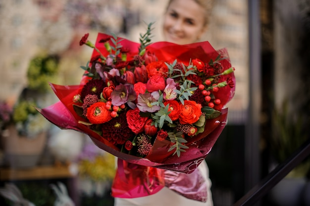 Girl stands with a completely red bouquet