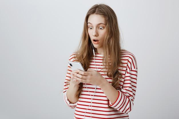 La ragazza fissa il cellulare sorpresa, leggendo notizie scioccanti