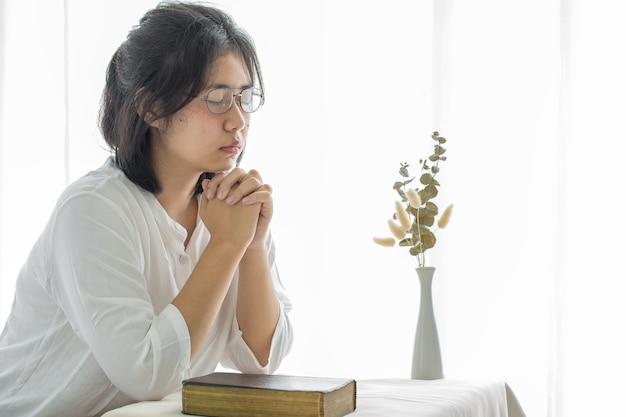 女の子は家にいて神を祈り、崇拝します。祈りの少女は、コロナウイルスの危機のために家から礼拝し、祈ります。家の教会、オンラインの教会、祈る手、家での礼拝