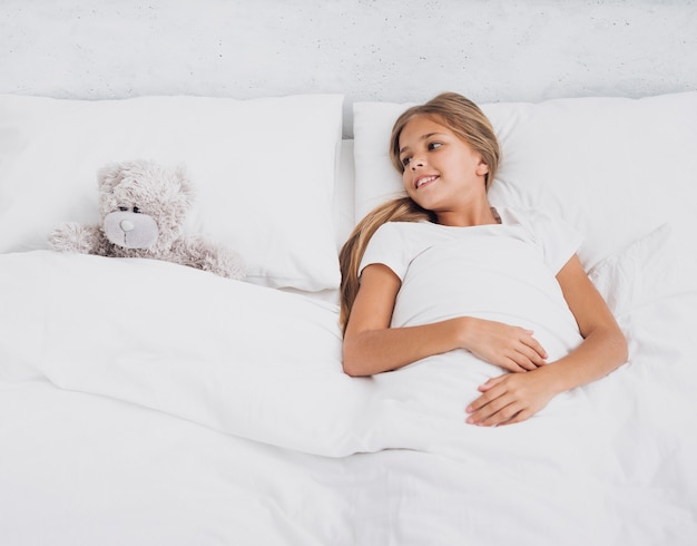 Girl staying in bed with her teddy bear