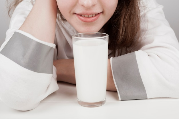 Girl staying next to a glass of milk