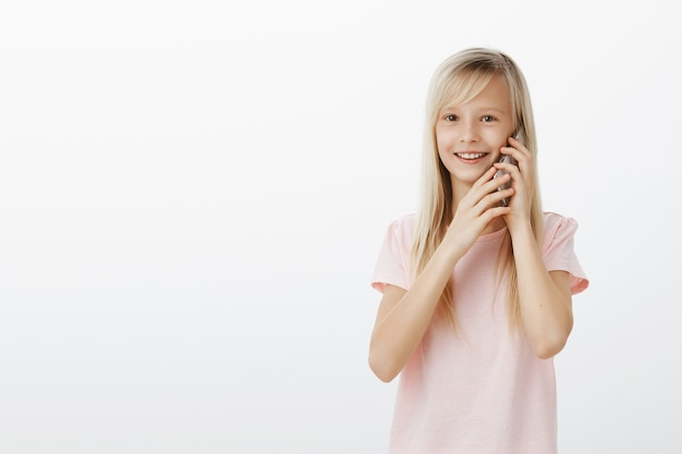 Girl staying in touch with grandparents who live far away. portrait of pleased adorable young child in pink t-shirt, talking on smartphone and holding device with both hands, smiling broadly