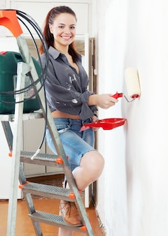 Girl  on stepladder paints wall with roller