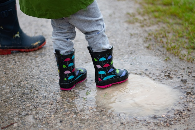 Girl stepping on puddles in the street with her boots