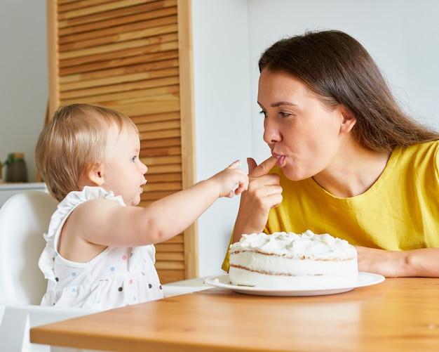 Девушка, приставшая палец к матери, пробует крем из торта, мать улыбается и облизывает палец