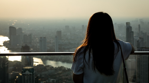 Girl stood on the roof of the building looking at the city full of dust and air pollution