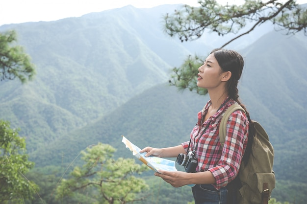 Girl stood to see the map on the hilltop in a tropical forest along with backpacks in the forest. adventure, hiking.