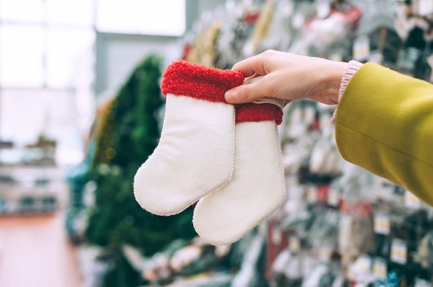 The girl in the store holds new year's socks in her hand.