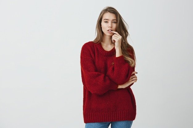 Girl in store tries to pick new shoes. studio shot of good-looking urban girl in red loose sweater standing with crossed arm and hand on lip, choosing from variants while looking focused
