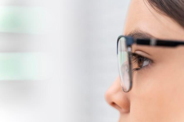 Ragazza in negozio che prova sugli occhiali si chiuda