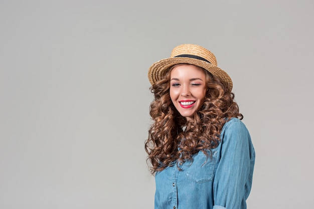 The girl in straw hat on gray wall