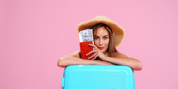 A girl in a straw hat holds tickets in her hands a trip a bag