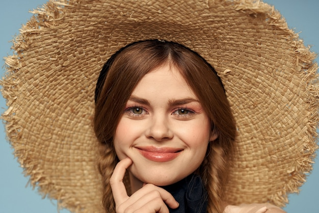 Girl in a straw hat portrait close-up pigtails fun red hair blue