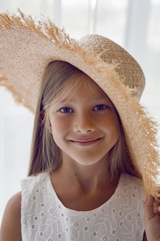 Girl in the straw hat stands at the window in the white room