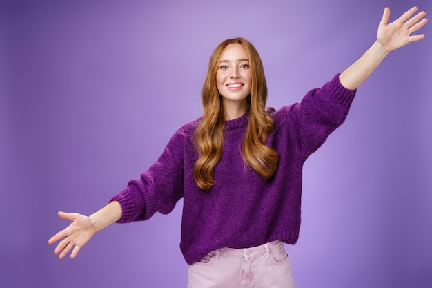 Girl stretched hands sideways to welcome and greet friend giving warm hug smiling broadly at camera standing joyful wanting cuddle over purple background, wearing violet sweater and pants. copy space