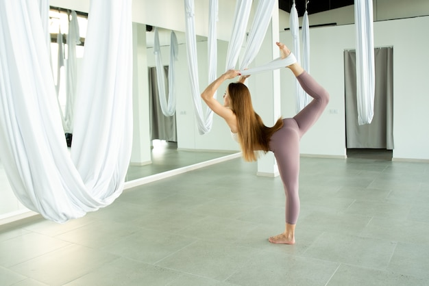 The girl stretches her leg with a hammock she is practicing fly yoga