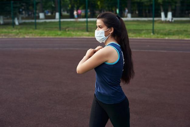 女の子はストレッチし、防護マスクで屋外でトレーニングする前に筋肉を伸ばします