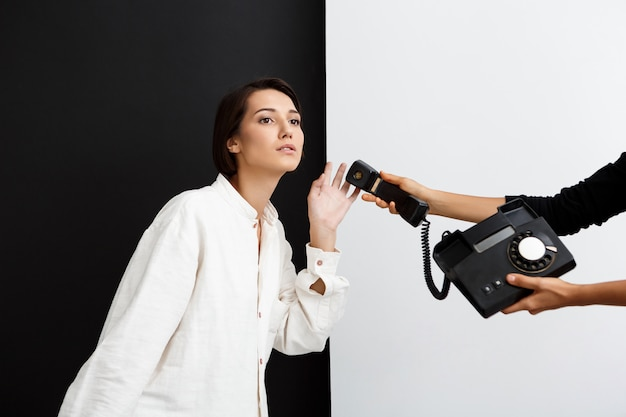검은 색과 흰색 벽에 오래 된 전화를 기지개하는 여자
