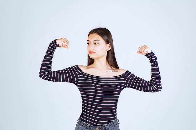Girl in striped shirt demonstrating her arm muscles.