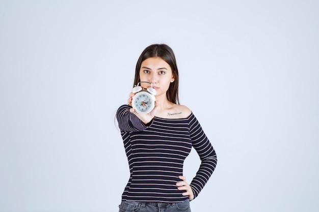 Ragazza in camicia a righe che tiene una sveglia e la promuove come un nuovo prodotto.