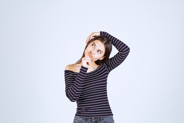 Girl in striped shirt holding her head.