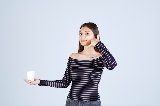 Girl in striped shirt holding a plastic coffee cup and asking for a call.