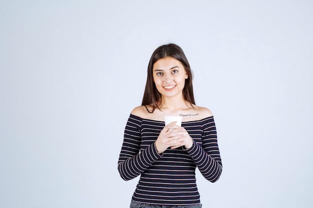 Ragazza in camicia a righe che tiene una tazza di caffè di plastica e sembra positiva.