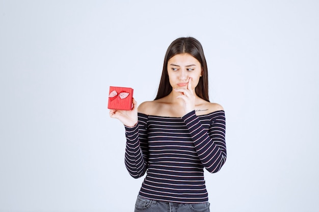 La ragazza in camicia a righe che tiene una confezione regalo rossa, sembra confusa e dubbiosa.