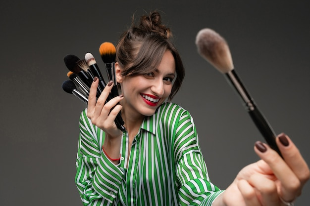 Girl in a striped shirt holds makeup brushes and holds out one brush on a dark wall