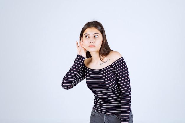 Ragazza in camicia a righe che ascolta o che fa pettegolezzi.