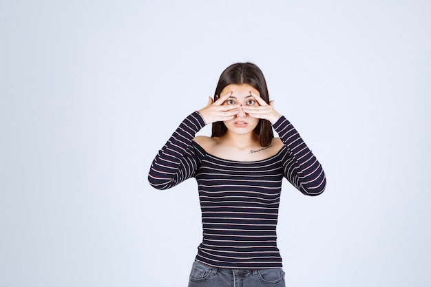 Girl in striped shirt looking through her fingers.