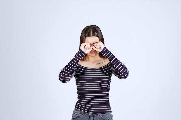 Ragazza in camicia a righe guardando attraverso le dita.