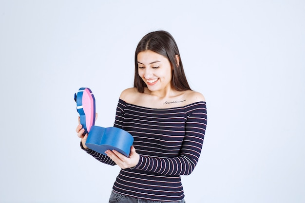 Girl in striped shirt opens a blue gift box and gets surprized.