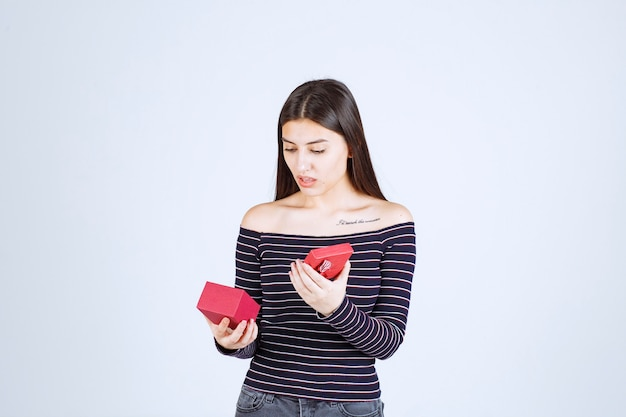 Girl in striped shirt opens a red gift box and gets confused.