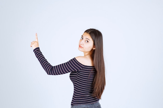 Girl in striped shirt pointing up and showing emotions.