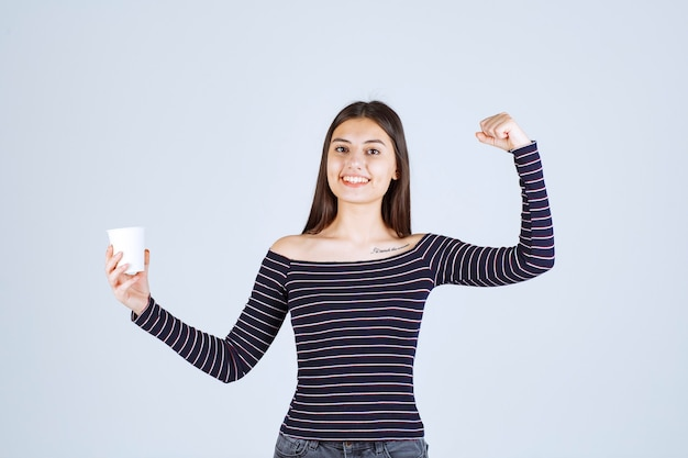 Girl in striped shirt showing her arm muscle and fist.
