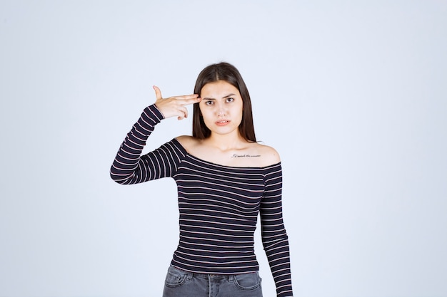 Ragazza in camicia a righe pensando e analizzando.