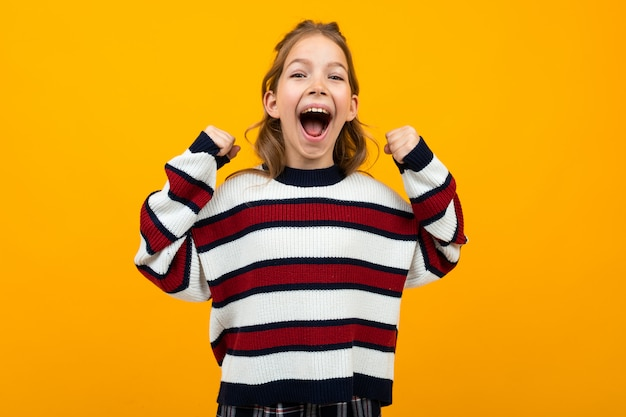 Girl in a striped sweater with wide open mouth shouting news on yellow